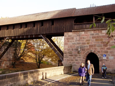 An old timber and stone covered bridge over a river in a public park in Nuernberg, where Rand's great grandparents may have once visited. The muscular angled timbers recall Rand Soellner's bracing in his work today.